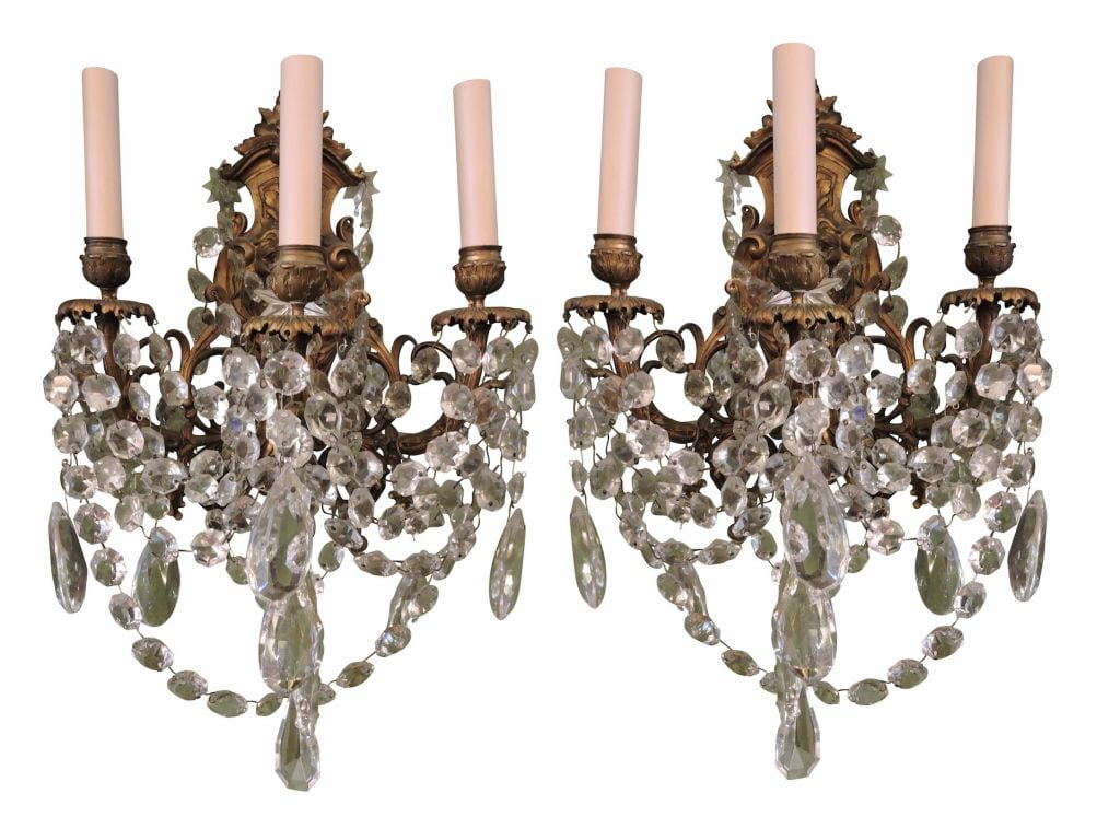 A pair of lion mask bronze sconces with 3 lights each and hanging crystals